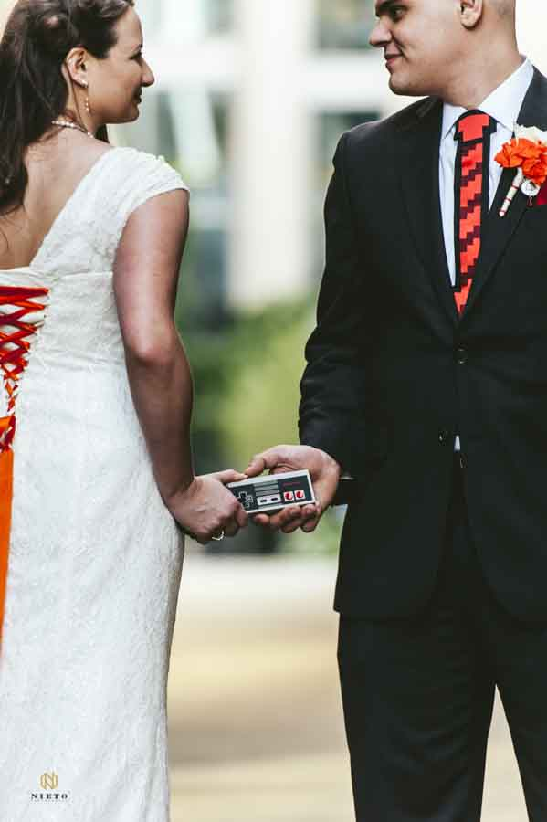 Bride and groom holding a Nintendo controller between them on their wedding day
