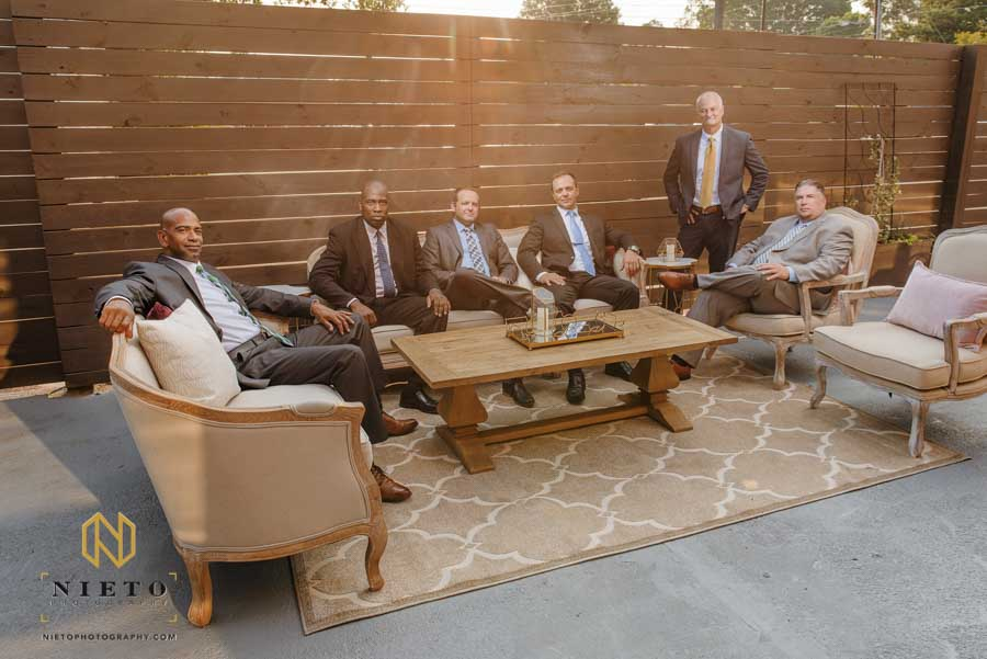 Portrait of seven men sitting around a table outside posing for a portrait