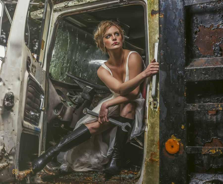 model sitting in a dump truck holding onto a wrench
