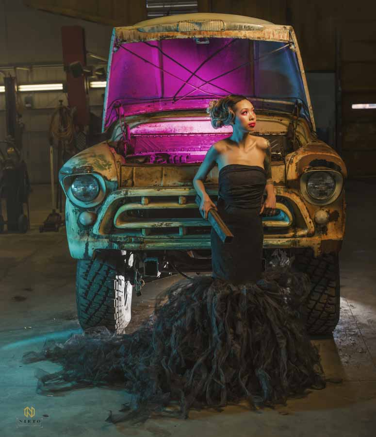model in black dress leaning on a truck