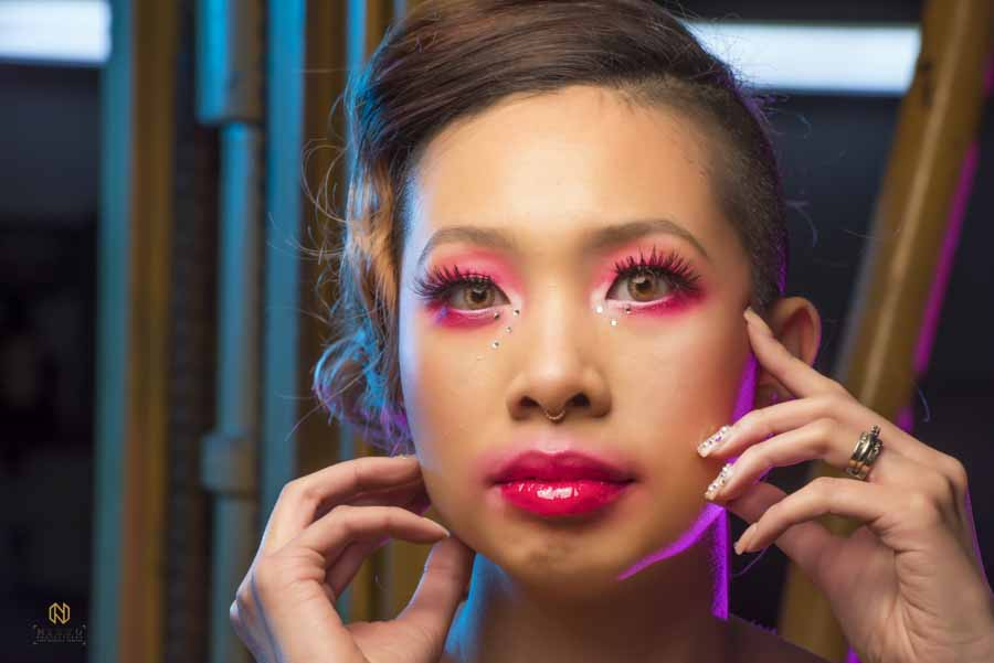 model with pink makeup on her face looking at the camera