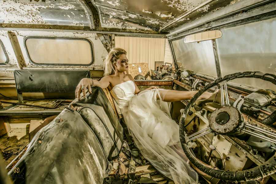 model leaning bach in a wedding dress inside a land rover