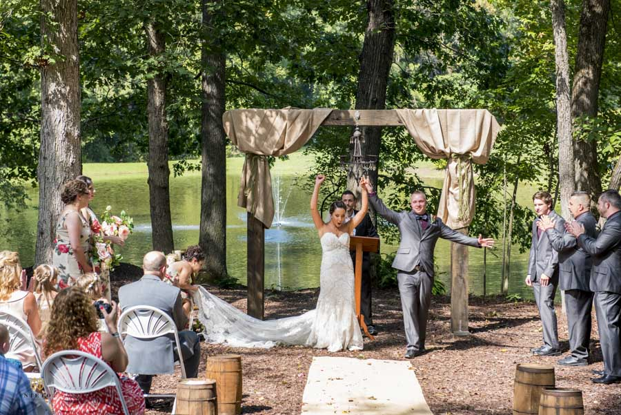 bride and groom with their hands in the air cheering after their wedding ceremony at chapel in the woods