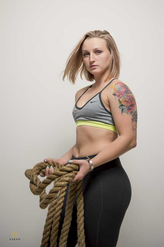 Softball player posing for a portrait while holding a battle rope