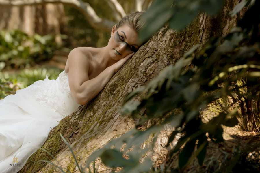model leaning against a tree in a wedding dress