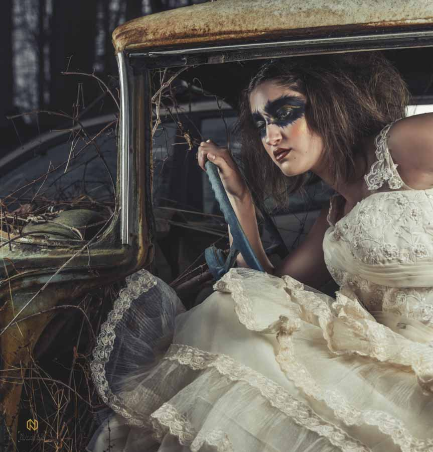 model in a rusted out car with black make up all around her eyes