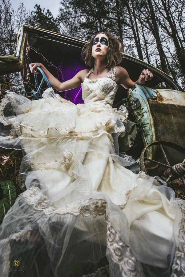 model sitting in a junk car in a wedding dress