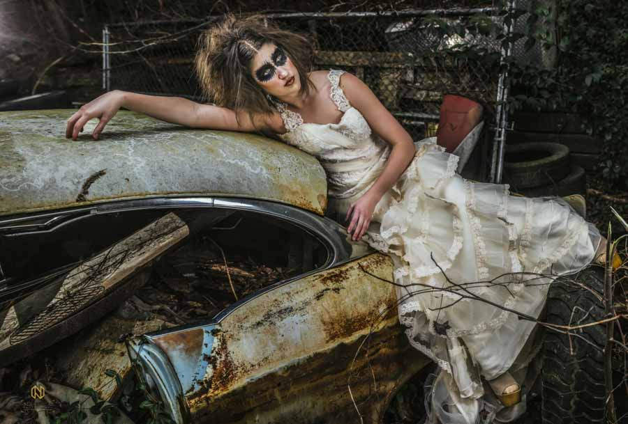 model laying on a car for an editorial bridal portrait