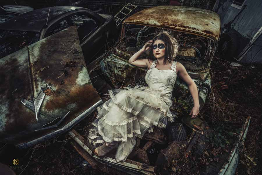 editorial bridal portraits of a model laying on a junk car