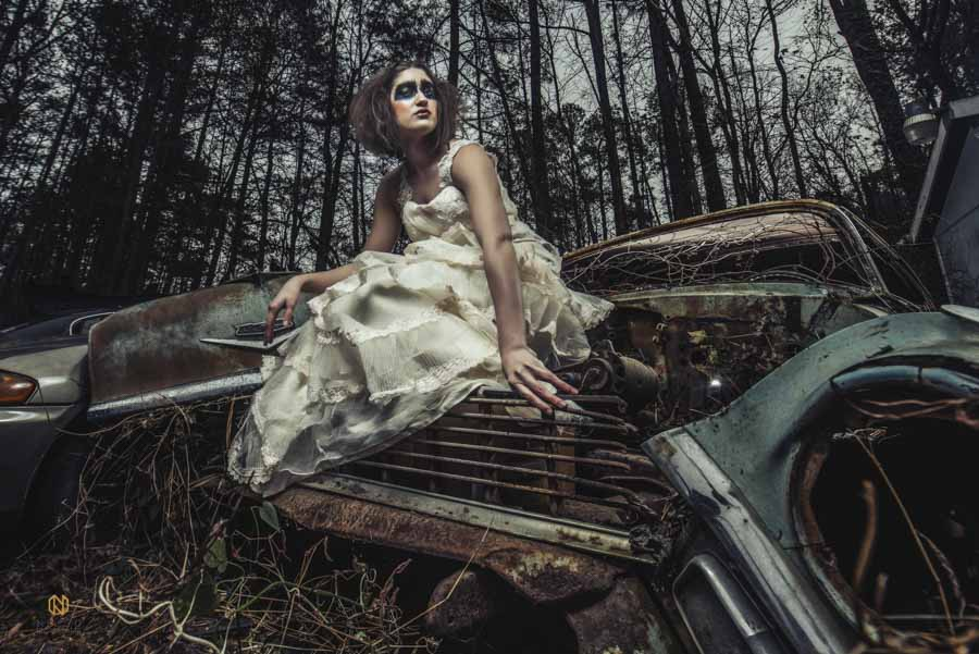 model sitting onto of an old car in a wedding gown
