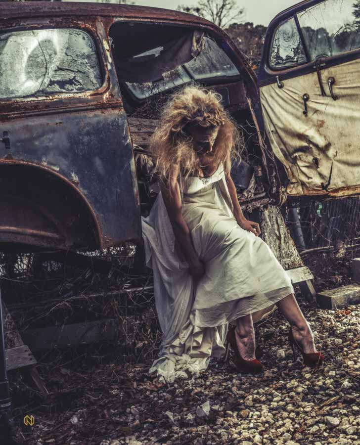 model adjusting her dress as she sits in a rusted out car for an editorial bridal portrait