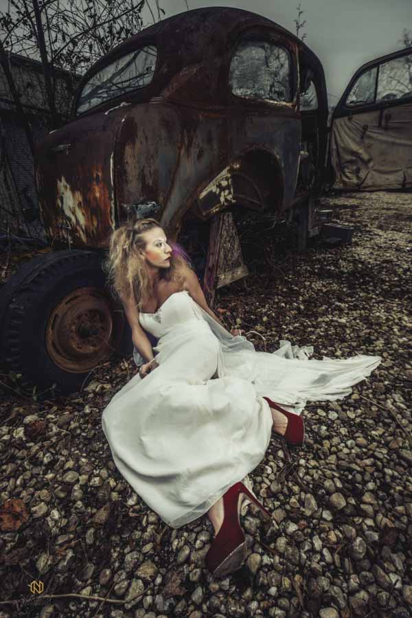 model laying against a rusted out old car