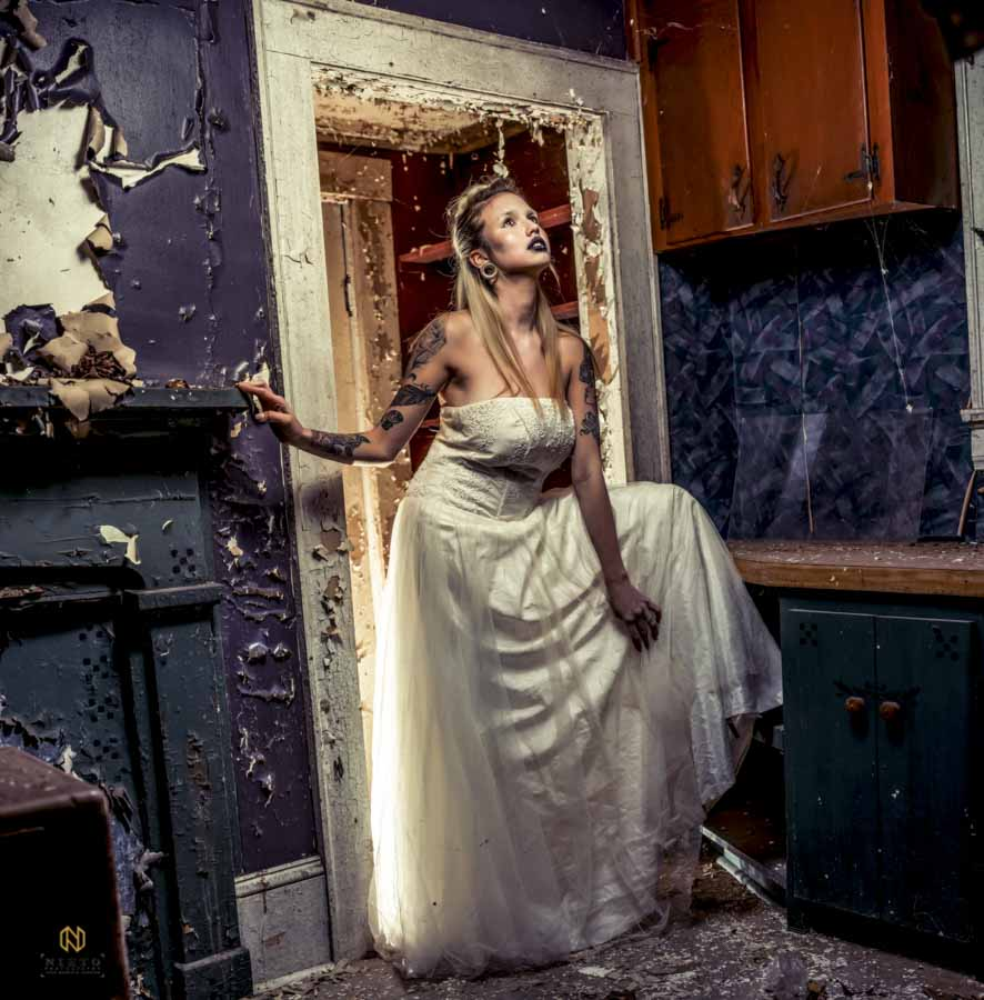 model standing in an abandoned home wearing black makeup