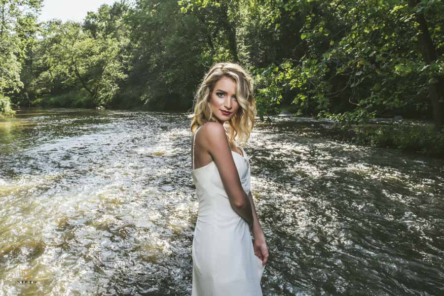 model holding on to her dress as she stands in the model of the Eno River