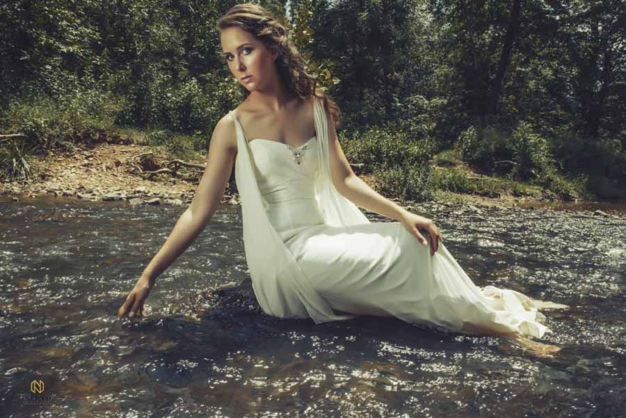 bridal model sitting in the river looking at the camera with her hand in the water