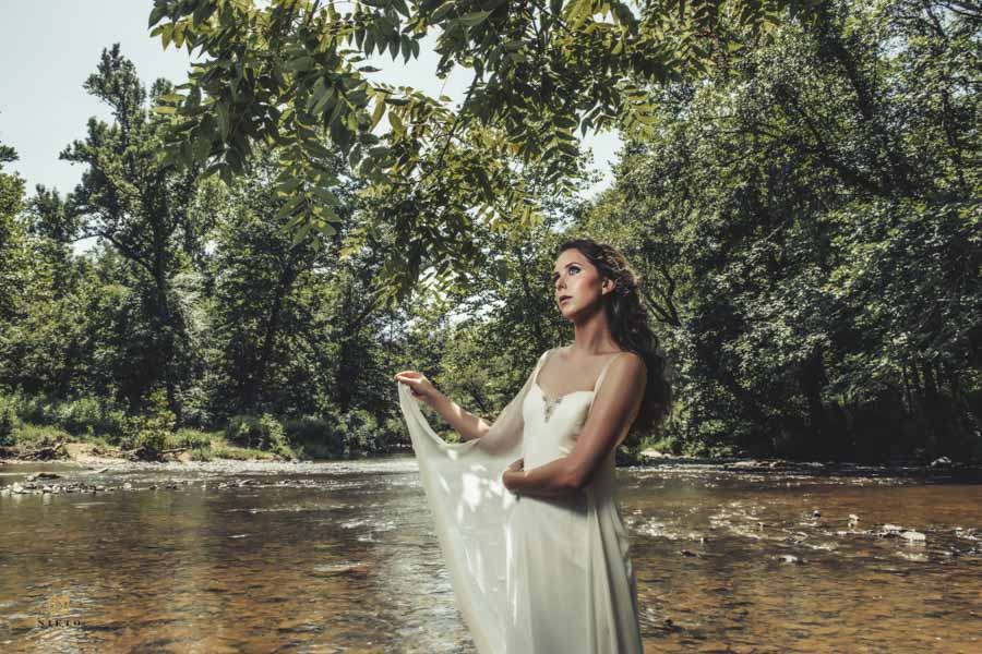 editorial bridal portrait of model holding on to dress while standing in the Eno river