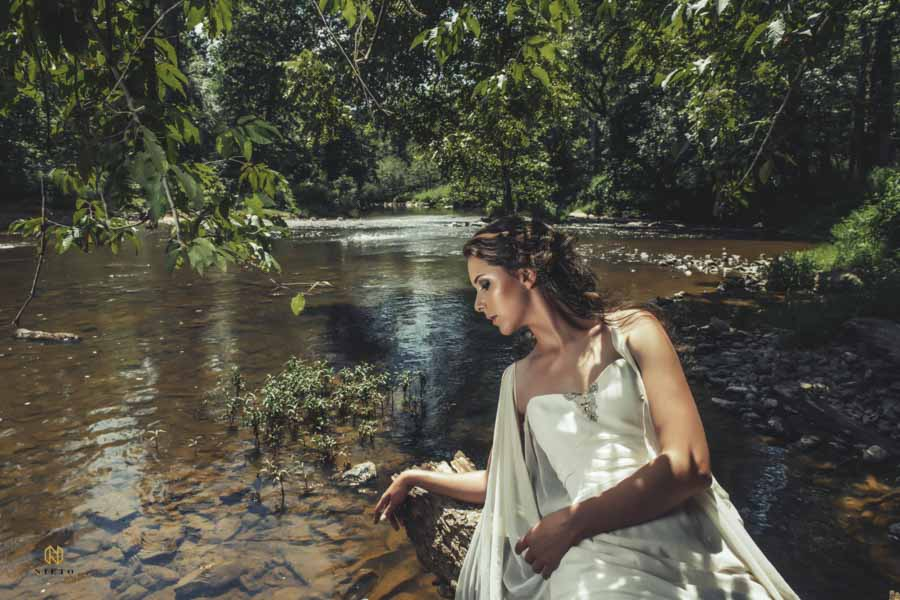Eno river bridal portrait with bride reclining on log with river in the back