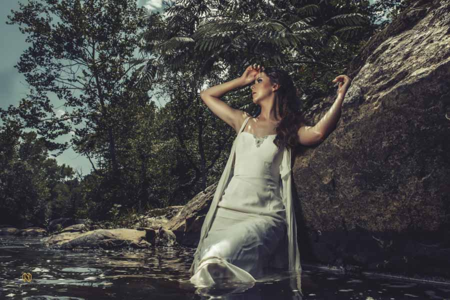 modeling posing as she is fainting against a rock in the Eno River