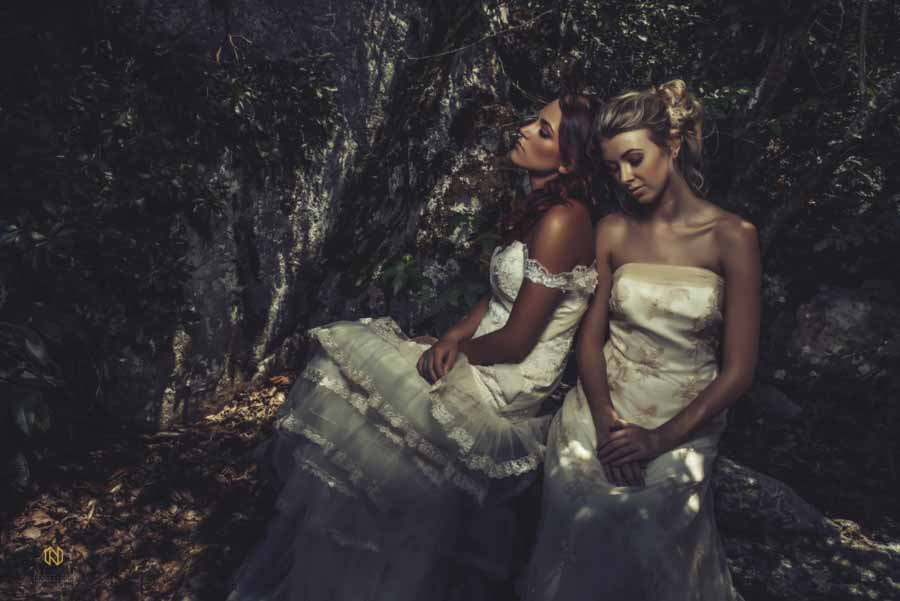 two bridal models leaning on each other sitting on the rocks at the Eno River