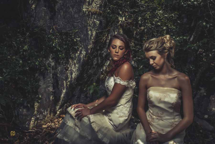 two models sitting in front of the rocks at the eno river looking down at the ground