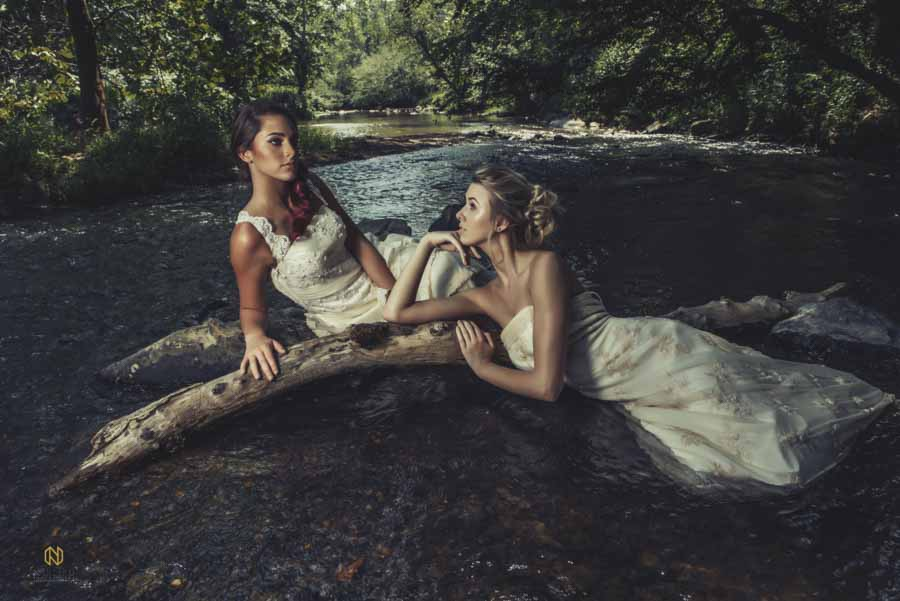 two bridal models laying in the river under trees looking past each other