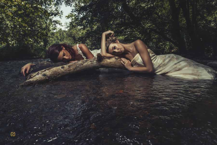 two bridal models laying in the river under trees with their heads down