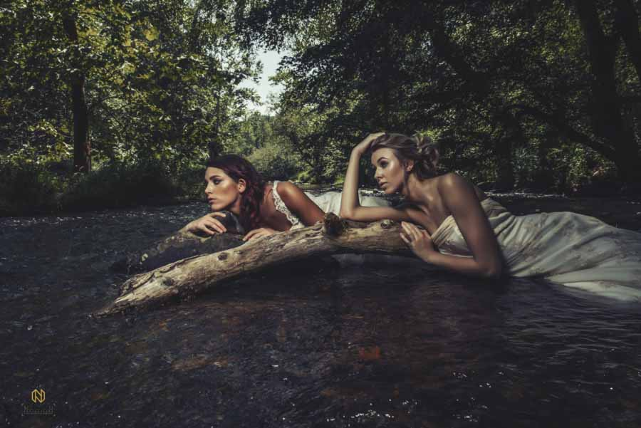 two bridal models laying in the river under trees on logs and rocks