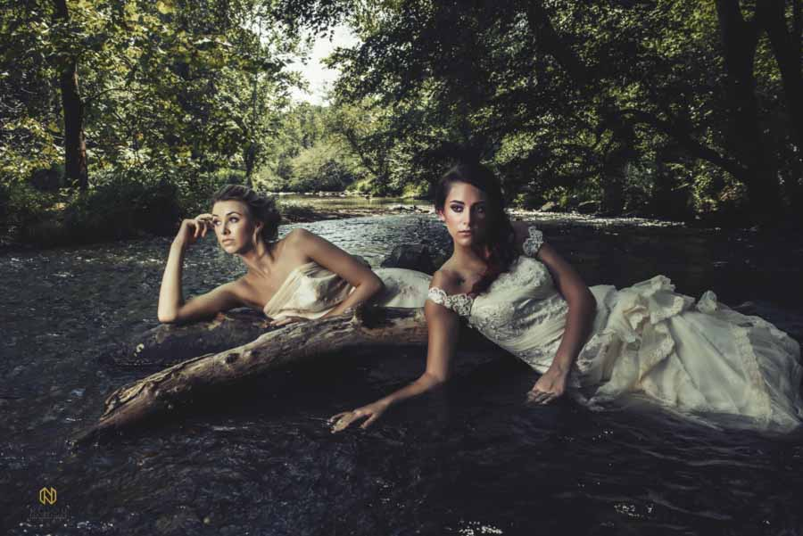 two bridal models laying in the river under trees