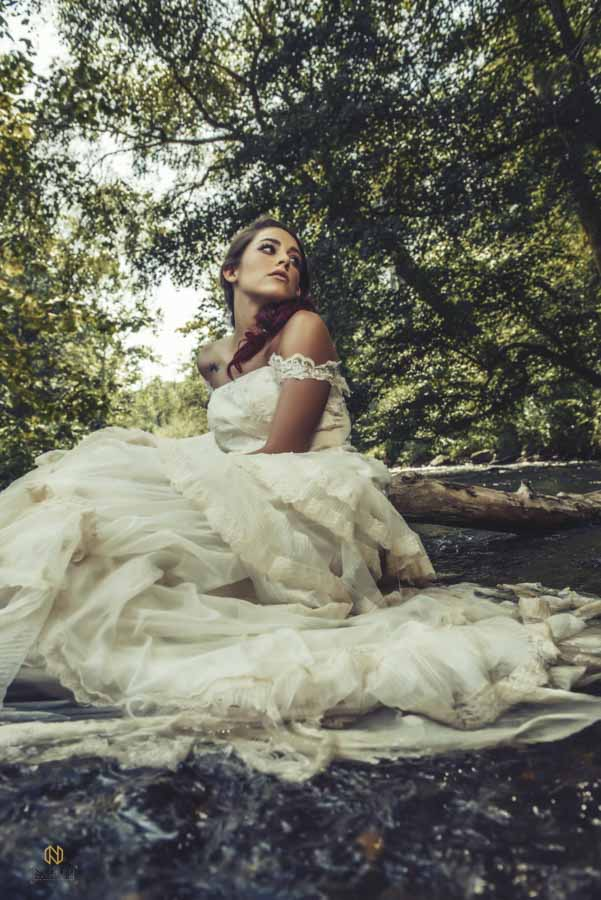 bridal model sitting in the Eno River in a wedding gown