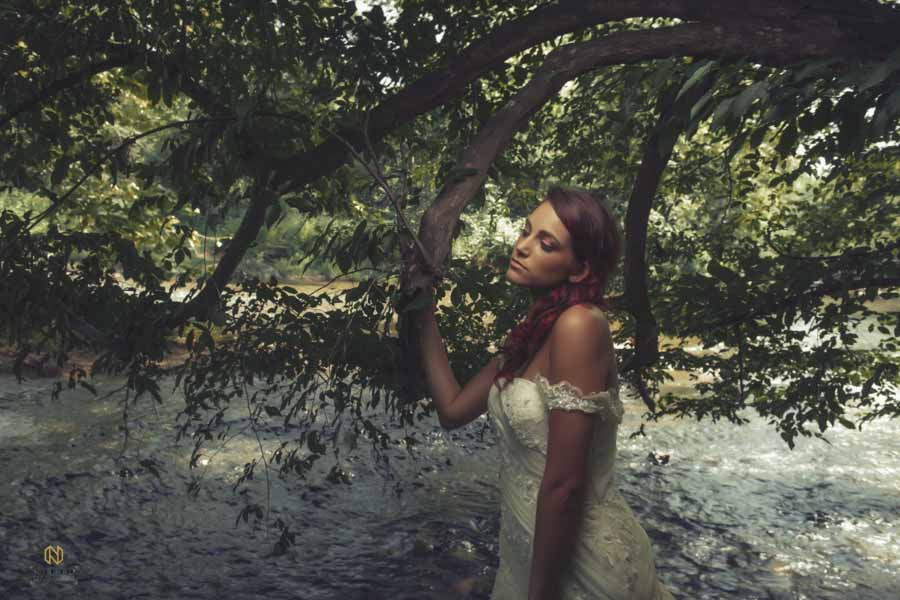 model leaning on a tree limp in the eno river