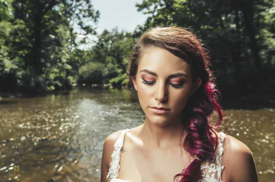 model standing in the eno river with her eyes closed showing off her eye shadow from Wink Hair and Makeup