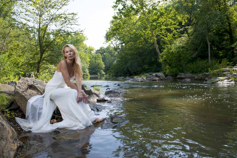 Eno River Bridal Portrait with bride sitting on rocks at the waters edge
