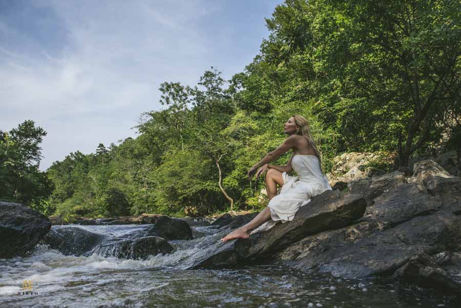 woman sitting on rock at the eno river in a wedding gown