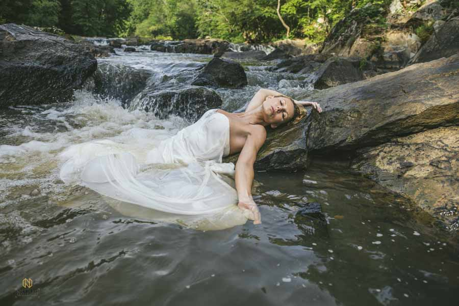 bridal model laying half in the water and half out of the water at the eno river