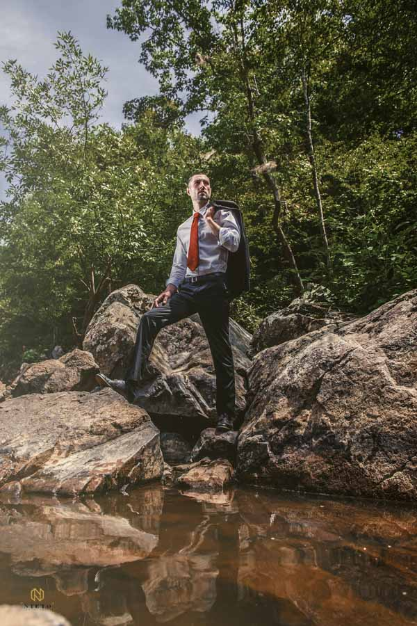 man standing in suit on the rocks at the eno river