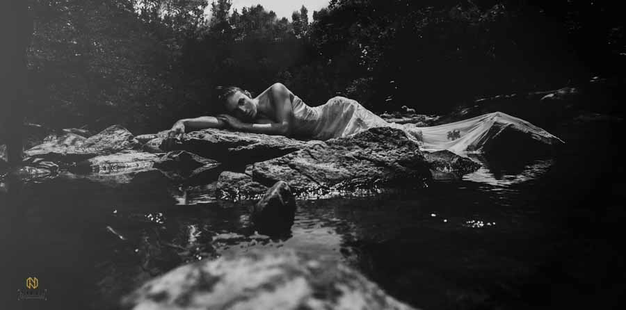 woman laying across rocks at the eno river in her wedding gown