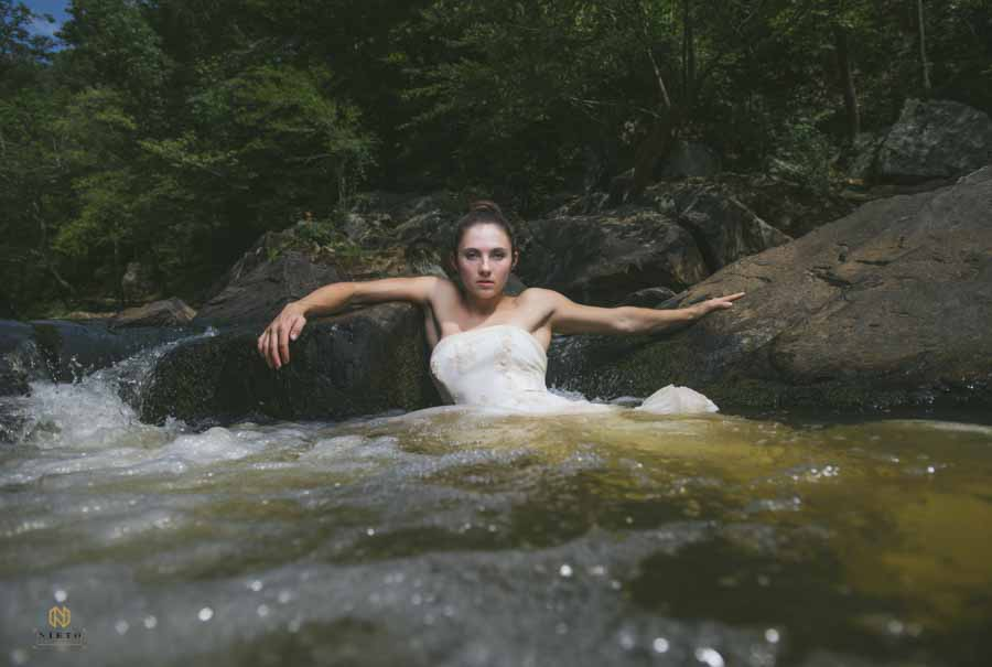 bridal portrait of woman in the eno river holding on to rocks