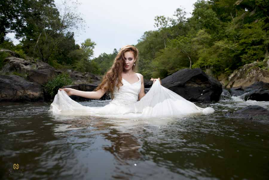 red headed bride holding her dress out of the water while she is in the Eno River
