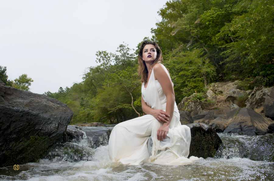 bridal model sitting on a rock in the eno river