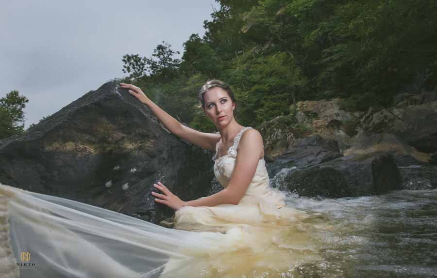 model in a bridal gown looking off into the distance as she holds on to a rock in the middle of the Eno River