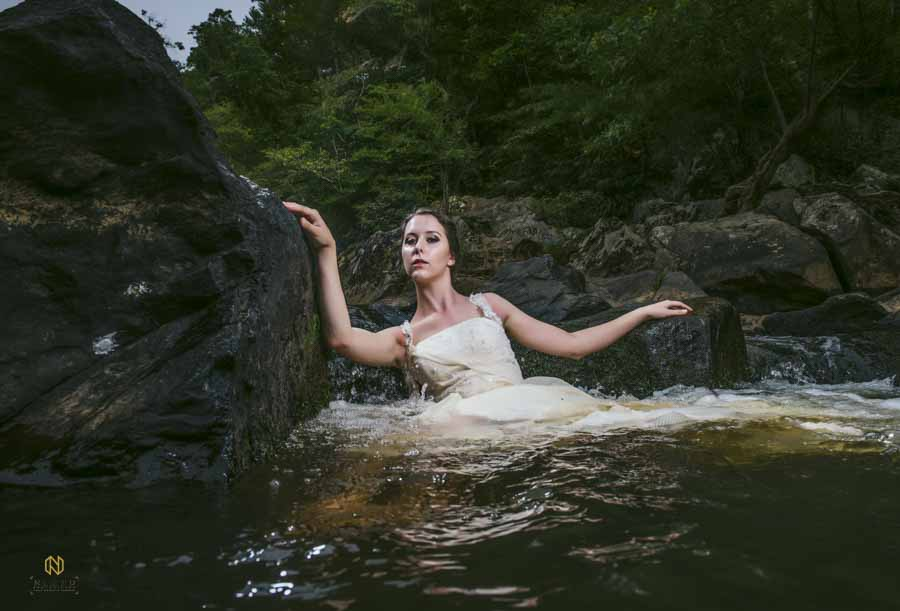 model in bridal gown holding on to rocks while she is in a river