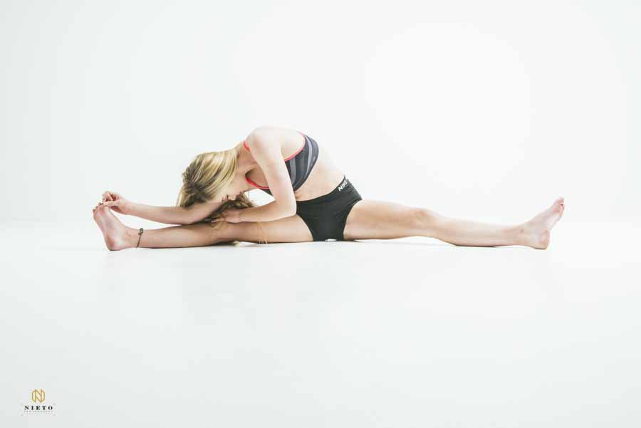 woman stretching out in a split in a white room