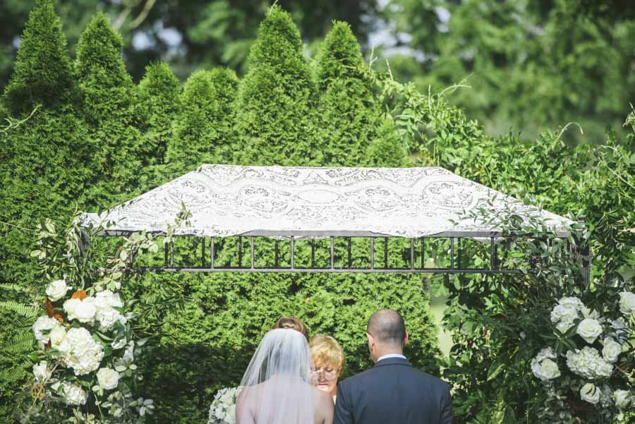 Bride and groom facing the minister under the chuppah at the Hudson Manor