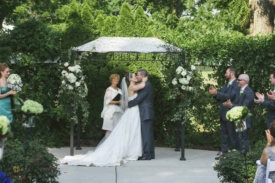 Bride and groom kissing under the chuppah in the garden at the Hudson Manor