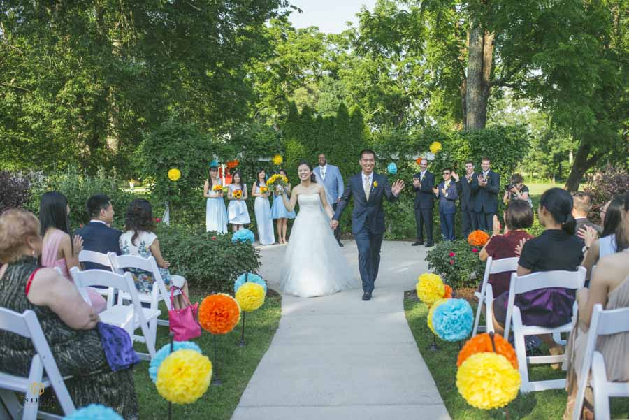 couple walking back down the aisle after their garden wedding ceremony at the Hudson Manor