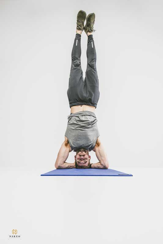 fitness portrait of a man doing a forearm stand in the White Space studio