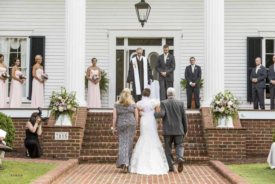 bride walking down the aisle with her mother and father in front of Rose Hill plantation