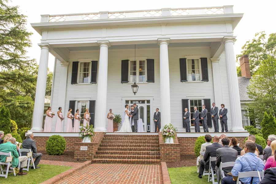 The bride and groom holding hands during their wedding ceremony on the steps of Rose Hill Plantation