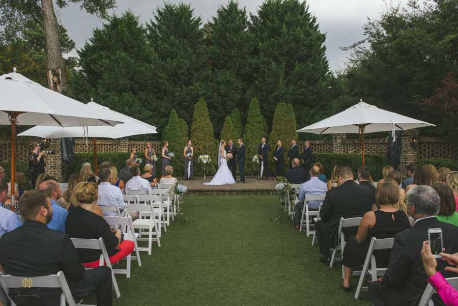 an outdoor sutherland wedding ceremony with umbrellas over peoples chairs