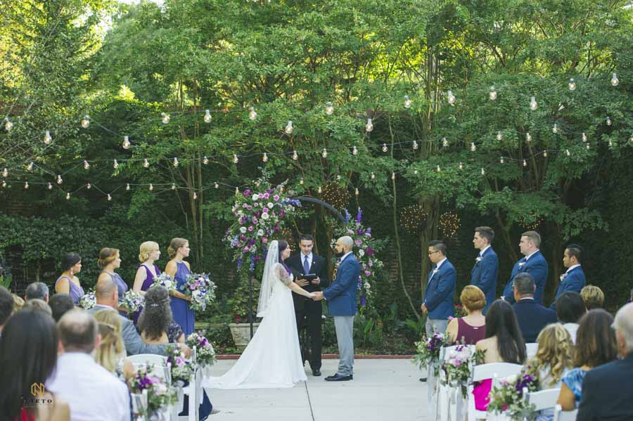 bride and groom holding hands during their vows at the garden on millbrook